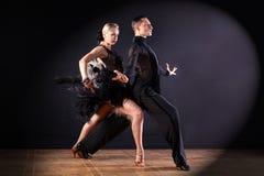 Dancers in ballroom  on black background Stock Photos