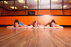 Dancers on dance studio floor. Three dancers wearing tutus resting on the dance studio floor royalty free stock image