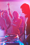 Dancers by dj turntables. Dancing girls enjoying party by turntables of deejay adjusting sound Stock Photography