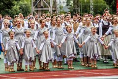 Dancers at Grand Folk dance concert of Latvian Youth Song and Dance Festival. RIGA, LATVIA - JULY 11, 2015: Dancers perform at the Grand Folk dance concert of royalty free stock images