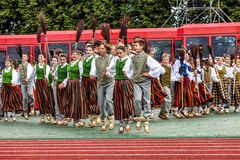 Dancers at Grand Folk dance concert of Latvian Youth Song and Dance Festival. RIGA, LATVIA - JULY 11, 2015: Dancers in traditional costumes perform at the Grand stock images