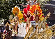 Dancers On Parade Float. SEATTLE, USA - JUNE 21, 2014 - Three women with feathered headdresses dance on the opening parade float of the 2014 Annual Fremont Stock Image