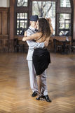 Dancers Performing Tango On Hardwood Floor In Restaurant. Full length of male and female dancers performing tango on hardwood floor in restaurant Royalty Free Stock Image
