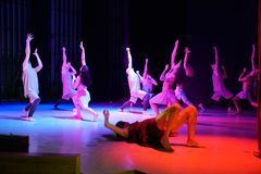 Dancers pulling hands up on the stage in red light royalty free stock photo