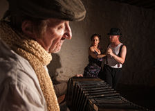 Dancers with Squeezebox Performer. Two European tango dancers turning as squeezebox performer plays Stock Photo