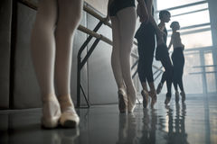 Dancers stands by the ballet barre. Young ballet dancers stands near the ballet barre at the ballet hall. Daylight falls on them through the large window Stock Photography