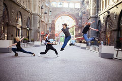 Dancers on the street. Two boys and two girls jumping and dancing on city streets royalty free stock photography