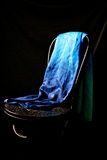 Dancers veil. A blue silk dancer's veil is draped over an old blak wooden chairs against a black background, it shimmers in the light Stock Photo