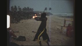 Dances With Fire. GHANA, BUSUA, APRIL 1976. Two Male Fire Dancers Performing Infront Of A Group Of Tourists On The Beach At Dusk With A Band Playing In The stock video