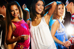 Dancing. Group of fashionable girls dancing energetically in night club Royalty Free Stock Photos