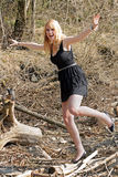 Dancing. A young woman dances happily in the sunlight on a tree stump Stock Photography