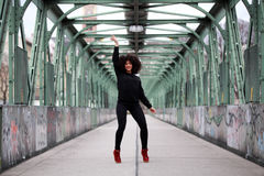 Dancing African girl with curly hair. Beautiful African woman standing on a bridge Stock Photos