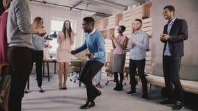 Dancing afroamericano felice del capo con gli impiegati al partito di team-building dell'ufficio, celebrante il movimento lento d stock footage