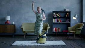 Dancing anziano felice con un aspirapolvere, divertimento domestico della donna stock footage