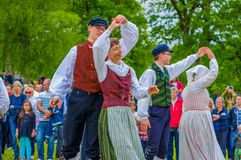 Dancing around the maypole in Midsummer. GOTHENBURG, SWEDEN - JUNE 19, 2015: Unknown dancers in traditional swedish dress dancing around the maypole for Royalty Free Stock Photos