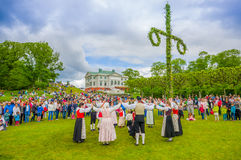 Dancing around the maypole in Midsummer. GOTHENBURG, SWEDEN - JUNE 19, 2015: Unknown dancers in traditional swedish dress dancing around the maypole for Royalty Free Stock Images