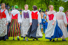 Dancing around the maypole in Midsummer. GOTHENBURG, SWEDEN - JUNE 19, 2015: Unknown dancers in traditional swedish dress dancing around the maypole for Stock Photo