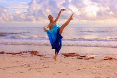Dancing as the sunsets. An attractive adult ballet dancer is dancing along the beach looking directly at the viewer with the setting sun adding a golden color Royalty Free Stock Photos