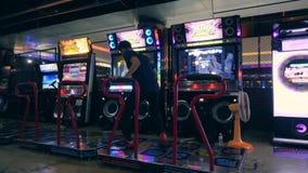 Dancing asiatico dell'uomo sulla rivoluzione Arcade Machine Pad di ballo nel centro commerciale di zona MBK del gioco 4K Bangkok, video d archivio