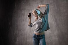 Dancing attractive woman listening to music in the mobile app. Girl music lover. royalty free stock photography