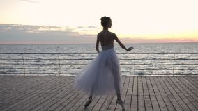Dancing ballerina in white ballet tutu and pointe on embankment above ocean or sea at sunrise or sunset. Young