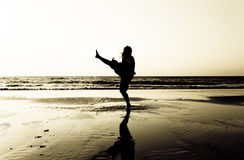 Dancing on beach. High contrast silhouette of a person dancing on an oceanfront beach Stock Photography