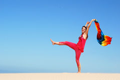 Dancing on the beach. A beautiful active teenage girl in pink clothes holding up a colorful shawl in the wind while dancing on a sand dune in sunshine after stock photo