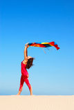 Dancing beach woman. A beautiful young caucasian white woman in pink clothes with relaxed  facial expression dancing with a big colorful shawl on a sand dune in Royalty Free Stock Image
