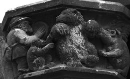 The dancing bear. Shot in black and white. Placed on the facade of this historic building, sculpture on the capital representing a man playing music for some Stock Photo