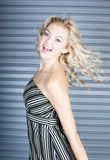 Dancing beautiful blond woman. Beautiful tall thin ecstatic woman with steel door background Stock Photos