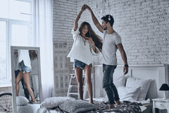 Dancing on the bed. Full length of beautiful young couple holding hands and smiling while dancing on the bed at home stock photo
