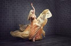 Dancing biondo di fascino della donna in un abito alla moda immagini stock libere da diritti