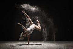Dancing biondo grazioso nel colore bianco della polvere fotografia stock