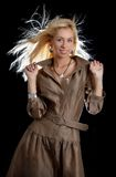 Dancing blond in brown dress Stock Photography