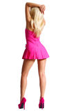 Dancing Blonde Girl in Short Pink Dress and High Heels. On her Sexy Legs isolated on white, Backside. Barbie Doll Royalty Free Stock Images
