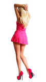 Dancing Blonde Girl in Short Pink Dress and High Heels. On her Sexy Legs isolated on white, Backside. Barbie Doll Stock Photo