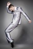 Dancing businessman in elegant gray suit.