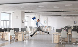 Dancing businessman in office room . Mixed media Stock Photo
