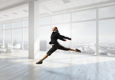 Dancing businesswoman in office . Mixed media Royalty Free Stock Photo