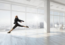 Dancing businesswoman in office . Mixed media Royalty Free Stock Photography
