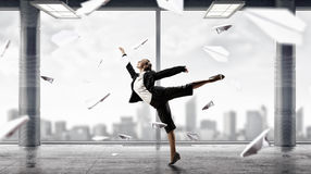 Dancing businesswoman in office . Mixed media Royalty Free Stock Images