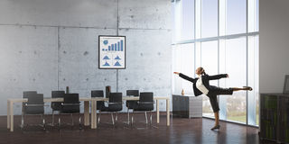 Dancing businesswoman in office room . Mixed media Royalty Free Stock Photo