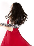 Dancing carefree. A back/side view of happy woman dancing and twirling in a red dress Stock Photography