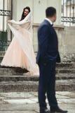 Dancing castana sorridente della sposa sulle vecchie scale allo sposo bello w Immagine Stock