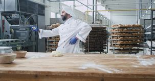 Dancing charismatic baker with beard in a stylish uniform in big bakery industry while listening music from wireless. Headphones stock video