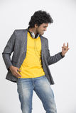 Dancing cheerful young Indian young urban man with headphone. On white background Royalty Free Stock Image