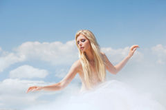 Dancing in the clouds. Beautiful blond woman dancing in the clouds Stock Image