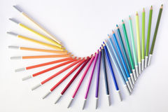 Dancing colored pencils. Wooden colored pencils arranged in a moving composition Royalty Free Stock Photo