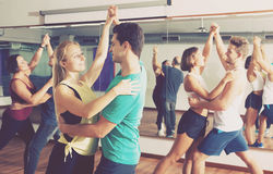 Dancing couples learning salsa Stock Images