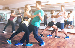 Dancing couples learning salsa. Group of young smiling people learning salsa at dance class. Focus on brunet man Stock Images